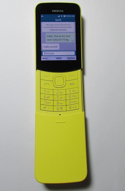 Das Bild zeigt das Nokia 8110 4G Tastenhandy in gelber Farbe mit der WhatsApp Anwendung.